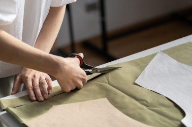 dressmaker-cut-pattern-in-tailor-workshop-closeup-K2VX3ED-scaled-1-scaled